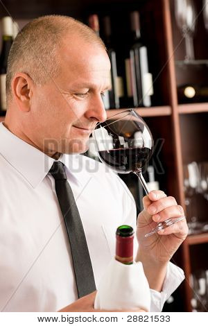 Waiter at bar smell glass of red wine in restaurant