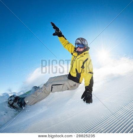 Snowboarding man at flattened piste - slope