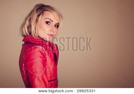Provocative Fashionable Blonde Woman dressed in a leather jacket and glancing sideways at the camera with raised eyebrow.