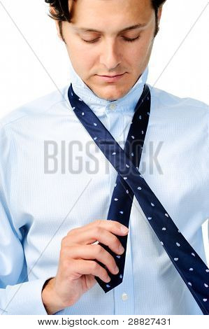 Businessman in blue shirt looks down at his necktie, isolated on white