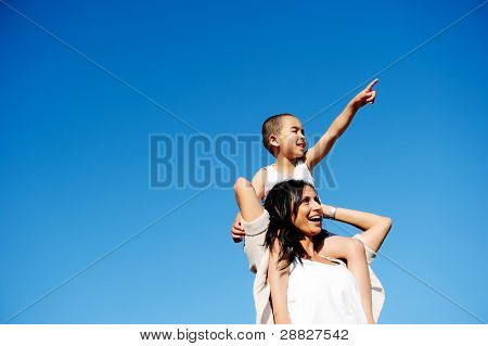 Mom and son happy and free outdoors in the blue sky. carefree cheerful concept