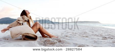 beach girl sits on the sand and opens her arms in a display of freedom and joy (panoramic large image with copyspace)