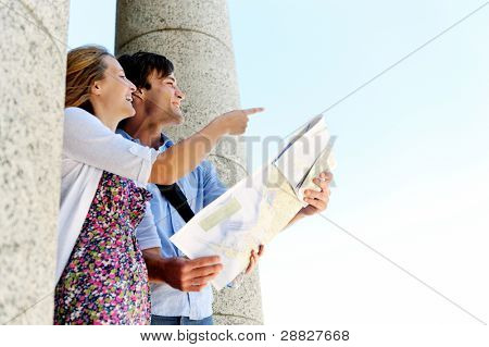 pareja de jóvenes turistas usa su mapa para determinar la dirección y el punto de la manera que desean ir