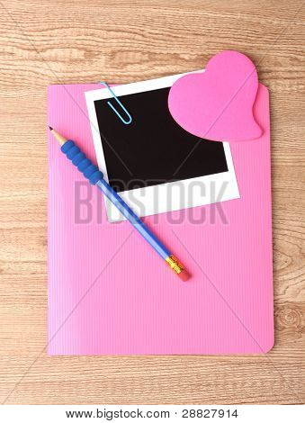 Photo paper and pink notebook on wooden background