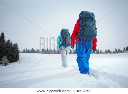 Backpackers walking through deep snowy field