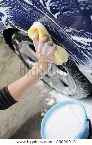 Man washing blue car with a yellow sponge and a bucket of soapy water.