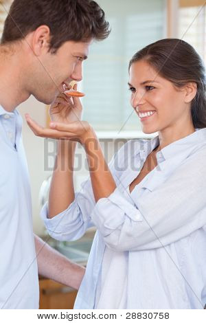 Portrait of a man tasting his wife's sauce in their kitchen