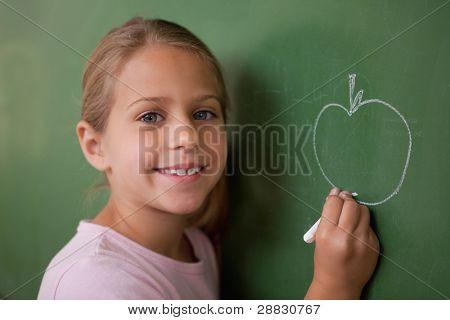 Smiling schoolgirl drawing an apple on a blackboard