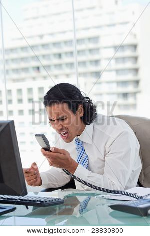 Portrait of a angry businessman shouting at his handset in his office