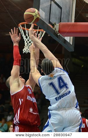 KAPOSVAR, HUNGARY - NOVEMBER 19: Jozsef Lekli (in white) in action at a Hugarian National Championship basketball game Kaposvar (white) vs. Paks (red) November 19, 2011 in Kaposvar, Hungary.