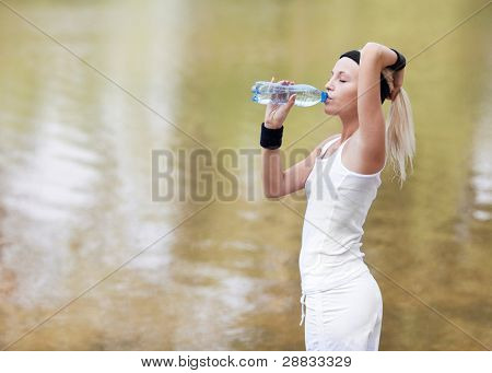 beautiful young blond sporty woman jogging in the park on a warm summer day and drinking water