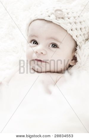 Cute 3-Months Baby wearing a  white knit hat