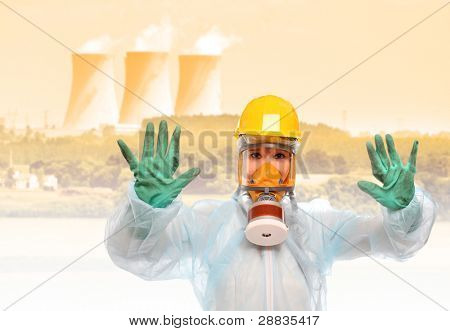 Worker in gas mask and protective suit against a radioactive air pollution from nuclear power plant.