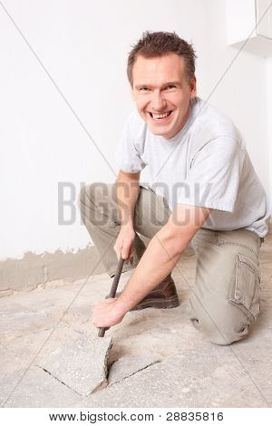 Happy manual worker disassembling old floor tiles
