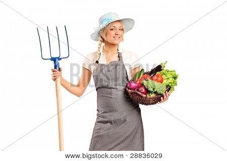 A female farmer holding a pitchfork and basket with vegetables isolated against white background