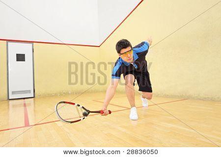 eine junge Squash Spieler Heizng eine Kugel in ein Squashplatz
