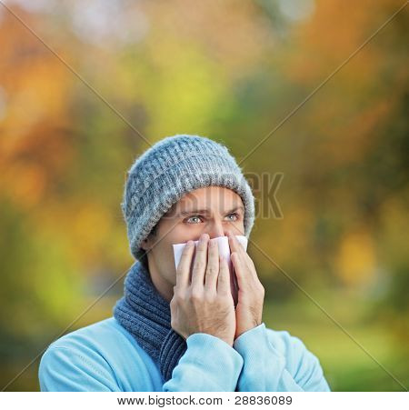 Infected man blowing his nose in tissue paper because of being ill or allergy