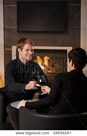Young romantic couple dating, sitting in front of fireplace at home, drinking red wine.?