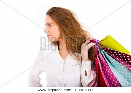 Beautiful young woman carrying shooping bags on white background