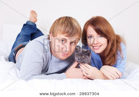 happy young couple on the bed at home with their cat (focus on the woman)
