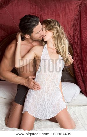 Young sexy naked heterosexual couple making love in bed