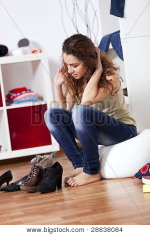 Beautiful young woman choosing shoes at the store