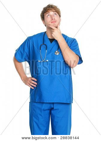 Male nurse thinking - man nurse or young doctor in blue scrubs looking up contemplative isolated on white background. Young Caucasian male medical professional.