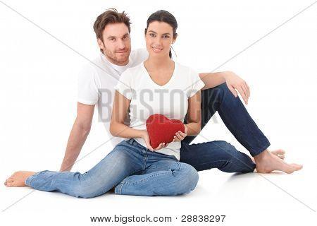 Loving Couple sitting on Floor, rotes Herz in der hand halten, lächelnd.?