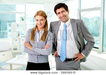 Two business partners in formalwear looking at camera in office