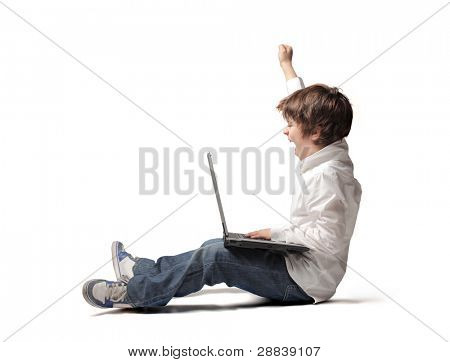 Triumphing child with a laptop on his knees