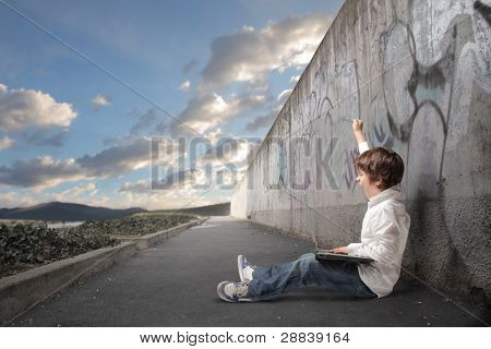 Triumphing child sitting on a city street and using a laptop