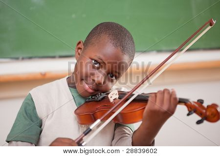 Schoolboy playing the violin in a classroom