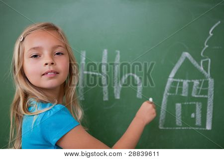 Schoolgirl learning the alphabet on a blackboard
