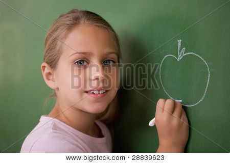 Schoolgirl drawing an apple on a blackboard