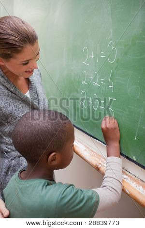 Portrait of a smiling teacher and a pupil making an addition in a classroom
