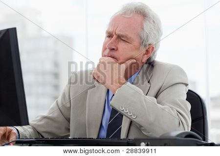 Focused senior manager working with a monitor in his office
