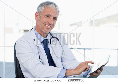 Smiling doctor working with a tablet computer in his office