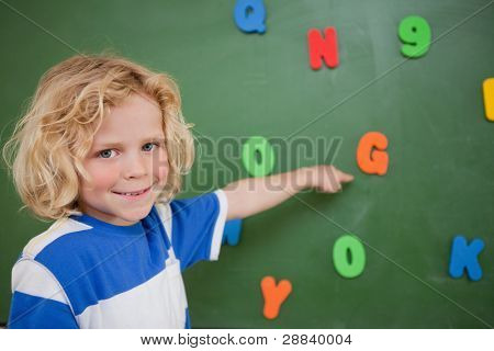 Schoolboy pointing at a letter on a blackboard