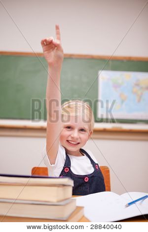 Portrait of a girl raising her hand in a classroom