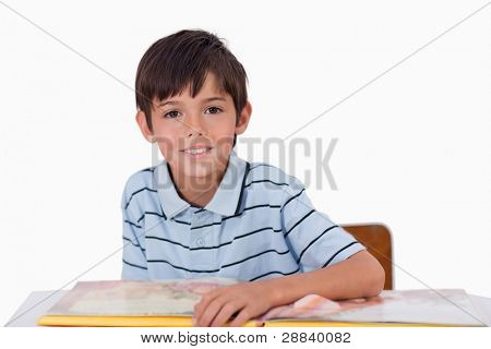 Cute boy reading a book against a white background