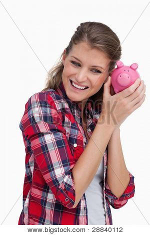 Portrait of a young woman shaking a piggy bank against a white background
