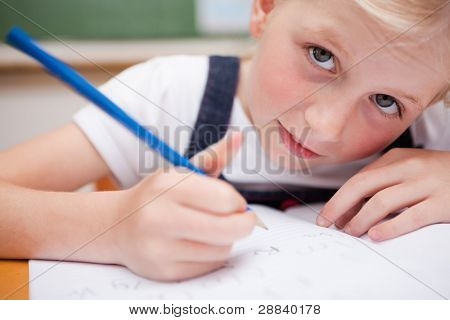 Close up of a serious schoolgirl writing something in a classroom