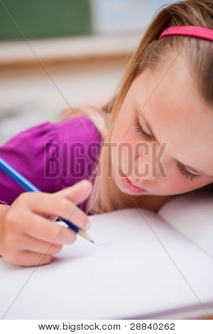 Portrait of a young schoolgirl writing in a classroom