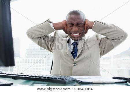 Entrepreneur having a headache while working with a computer in his office