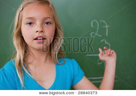 Little schoolgirl showing her result on a blackboard