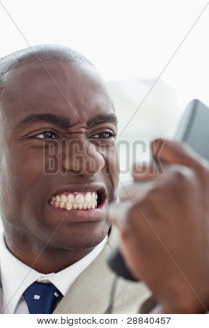Portrait of an angry businessman looking at his phone handset in his office