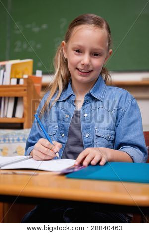 Portrait of a smiling schoolgirl writing in a classroom