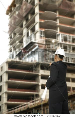 Designer Pointing At Building Under Construction