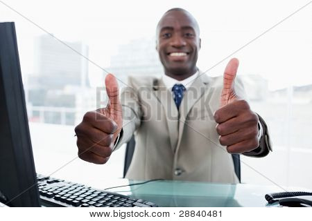 Entrepreneur working with a computer with the thumbs up in his office