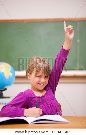 Portrait of a schoolgirl raising her hand in a classroom